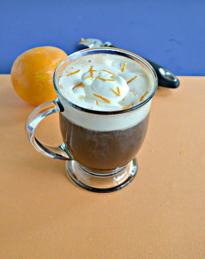 A clear mug filled with two thirds of coffee and topped with whipped cream and orange zest. Behind the mug is an orange and a zester.