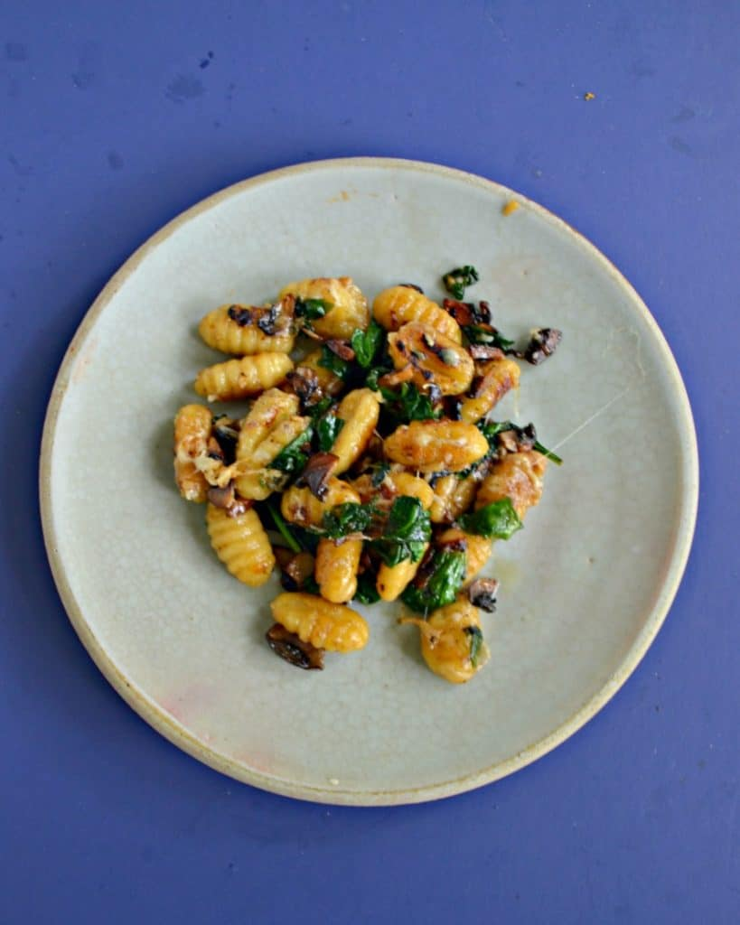 Top view of a plate with a pile of crispy gnocchi, wilted spinach, and cooked mushrooms.