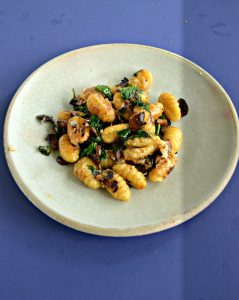 A plate mounded with browned gnocchi, wilted spinach, and mushrooms on a blue background.