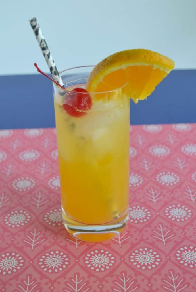 Black Eyed Susan: Tall glass with orange drink in it topped off with a cherry, orange slice, and black straw, sitting on a red placemat with a blue background.