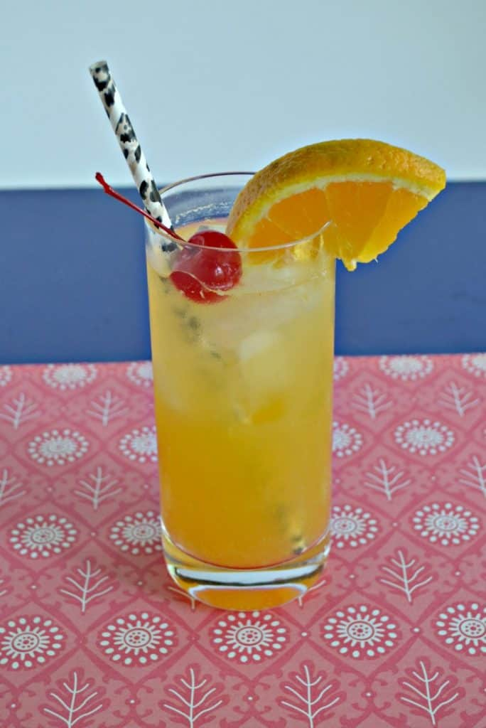 Tall glass with orange drink in it topped off with a cherry, orange slice, and black straw, sitting on a red placemat with a blue background.