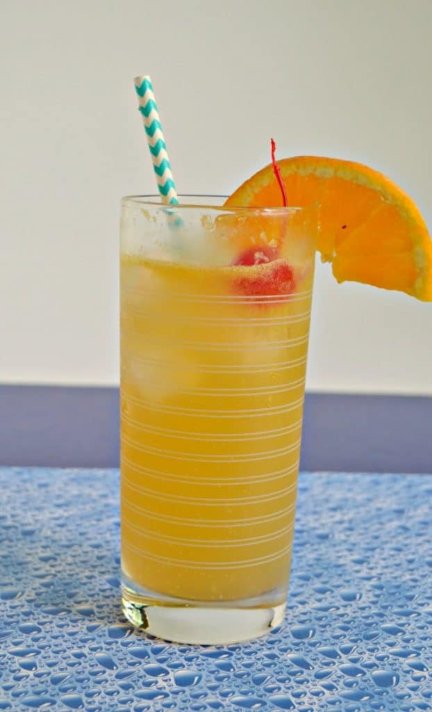 Close up view of orange cocktail with blue and white striped straw, orange slice, bright red cherry, on a blue bubble placemat.