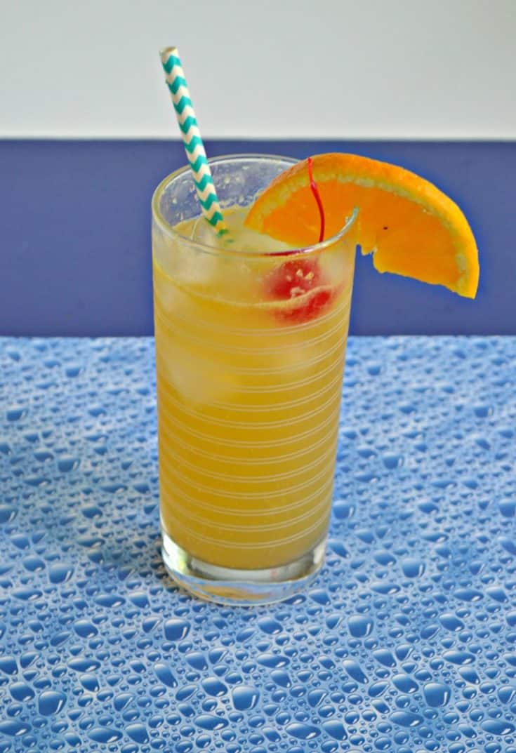 Side view of cocktail: Orange liquid with blue and white stripe straw sticking up, a bright red cherry, and an orange slice with a blue bubble background.
