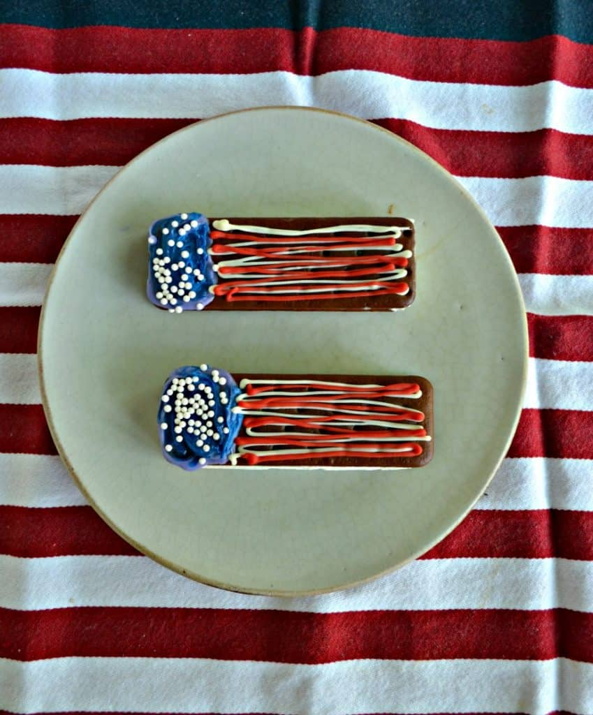 Two ice cream sandwiches sitting on a plate and decorated with blue chocolate on the left with edible pearls and red and white horizontal squiggles on nthe right to resemble a flag. Sitting on a red and white tablecloth.