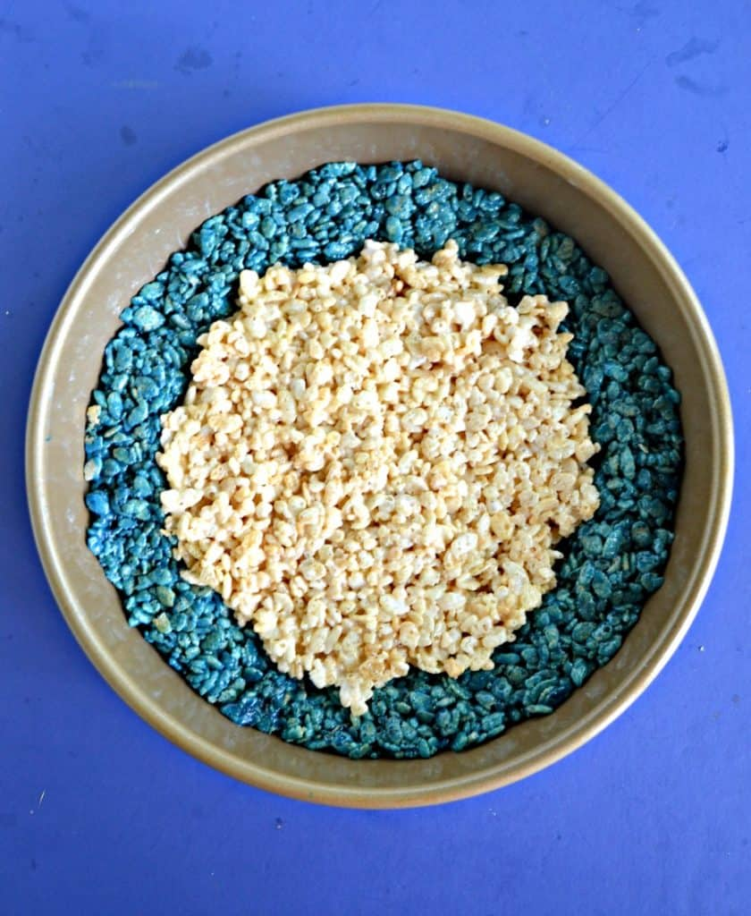 A cake pan with blue rice krispies around the outer edge with regular rice krispies treats in the center on a blue background.