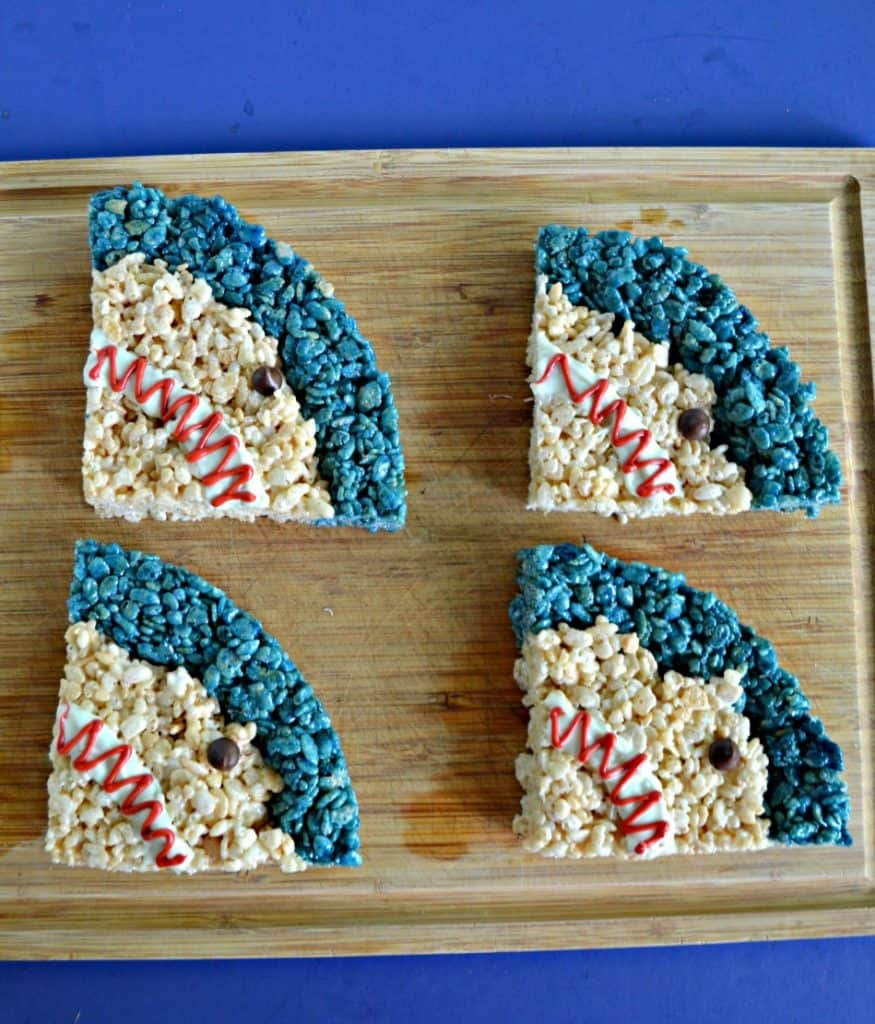 A cutting board with four shark heads on it. Each is a quarter of a circle with a blue strip on top and regular rice krispies treats filling in the rest with a white mouth and angry red squiggle and chocolate chip eye.