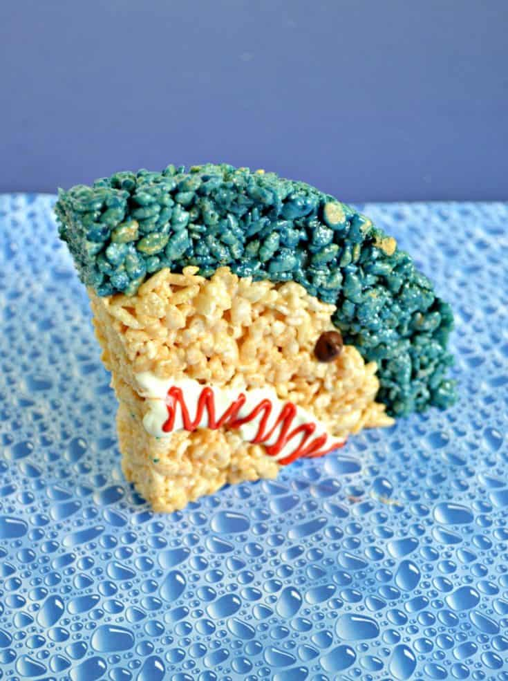 Blue bubble background with a shark rice krispie treat on it (A quarter of a circle with a small blue stripe at the top, regular rice krispies for the rest, a white mouth with red squiggle, and a chocolate chip eye.