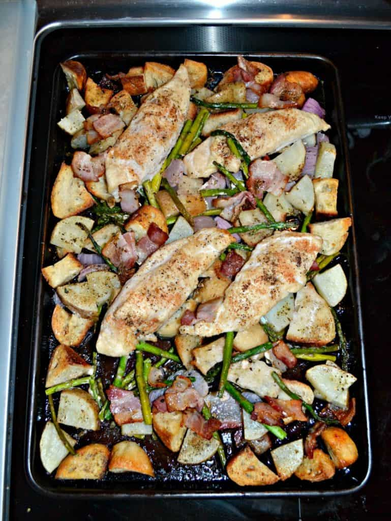 A sheet pan scattered with potatoes, sourdough croutons, chicken breasts, and fresh rosemary.