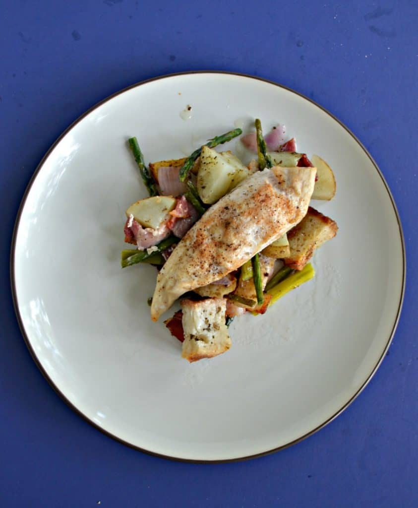 A plate piled with asparagus, potatoes, and a chicken breast on top on a blue background.