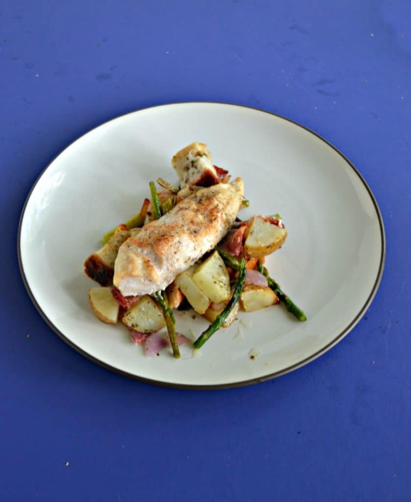 A plate topped with potatoes and asparagus with a chicken breast on top on a blue background.
