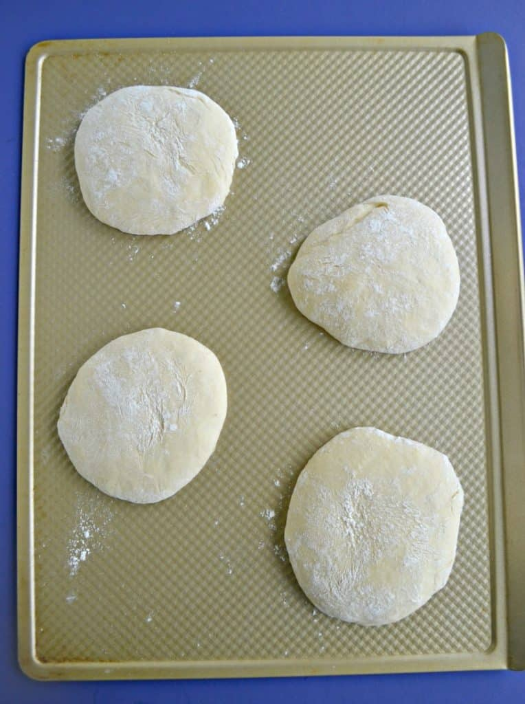 A cookie sheet with four mounds of pizza dough on it.