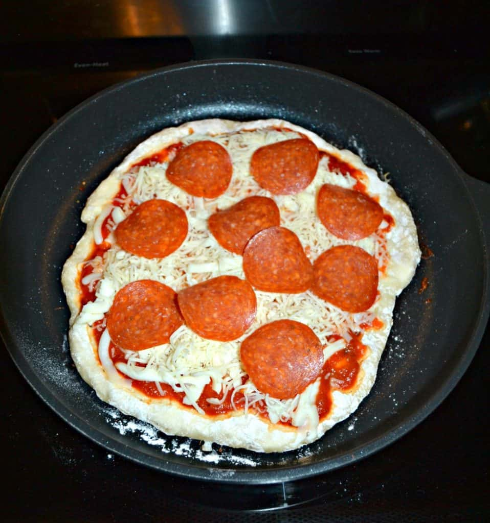 A skillet filled with a pizza crust topped with cheese and pepperoni.