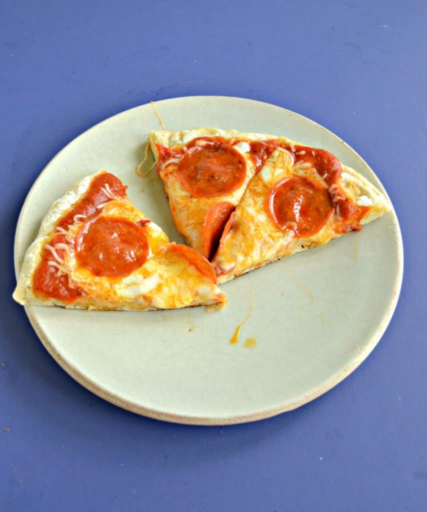 A plate with 3 slices of pepperoni pizza on a blue background.