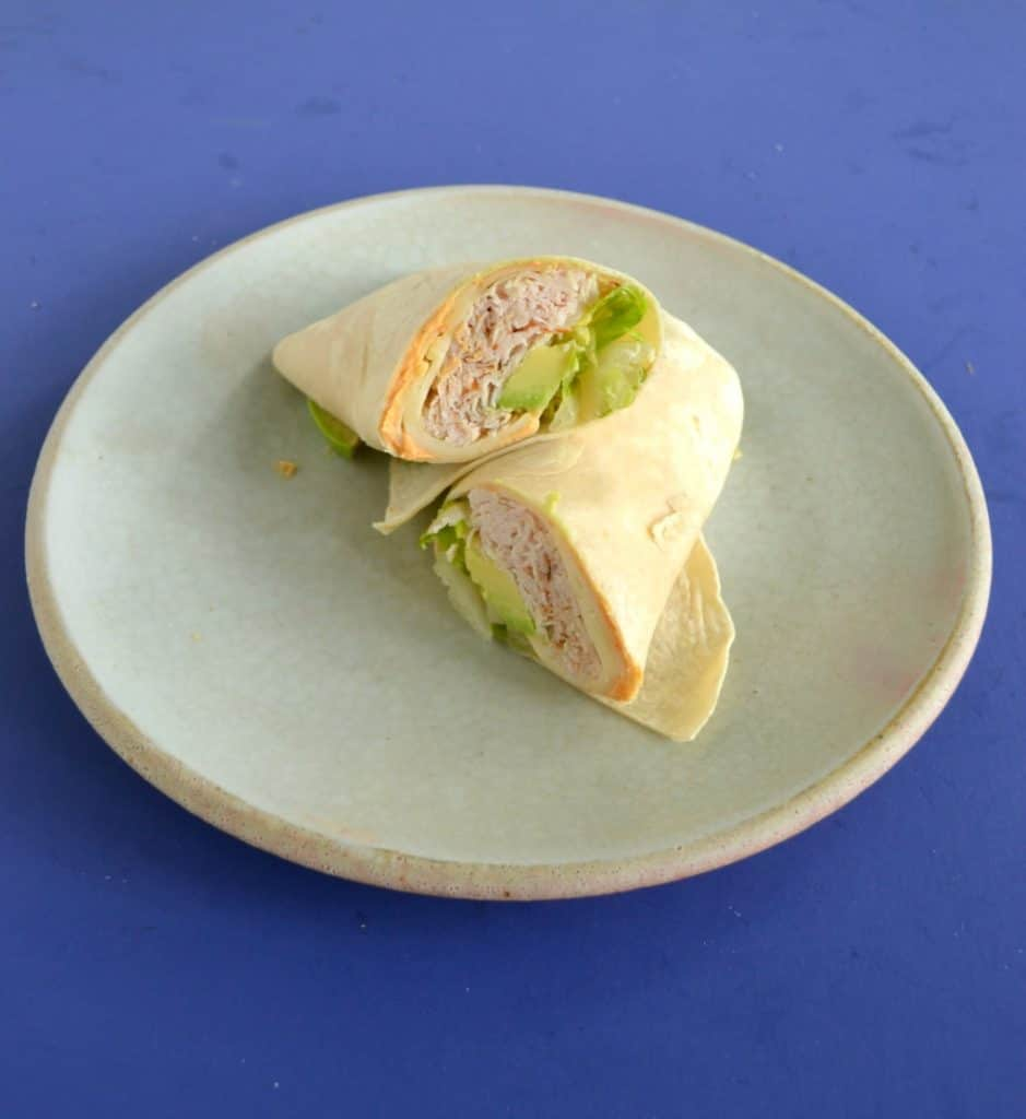 A plate with a turkey wrap on it, cut in half, and stacked on top of each other.