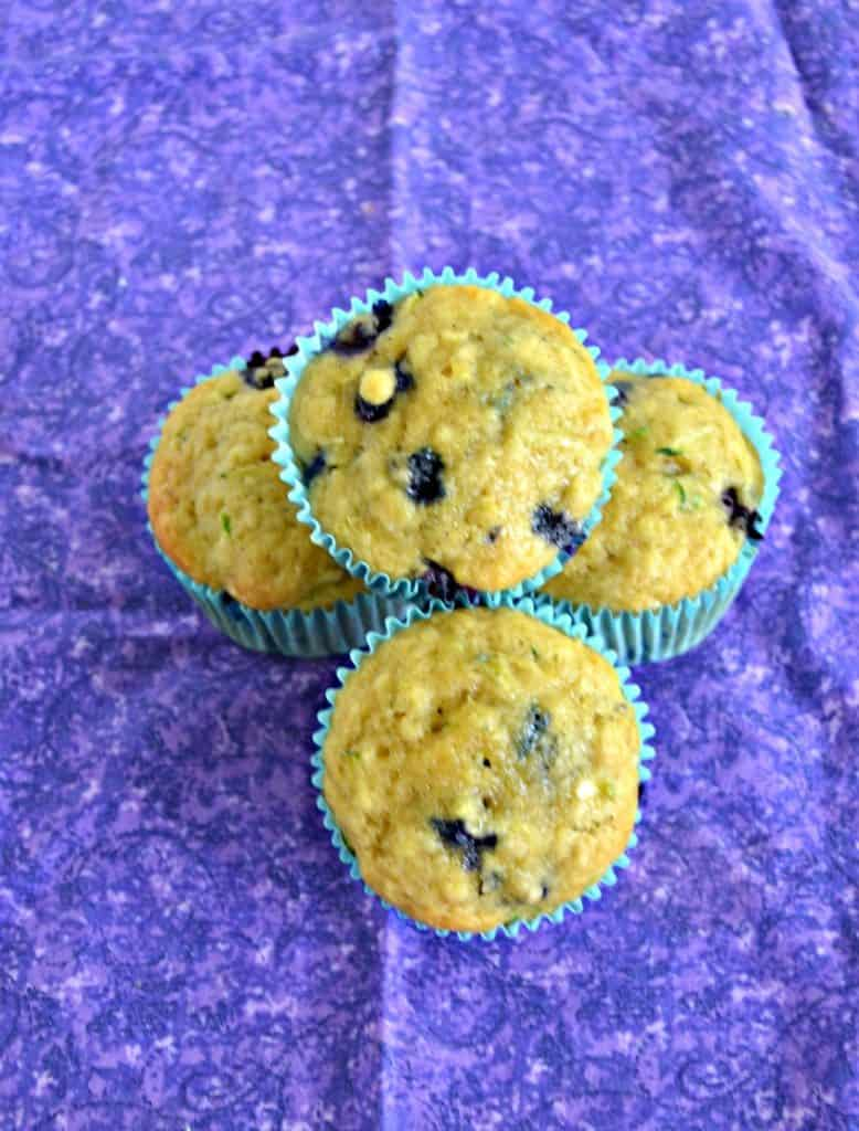 Top view of three muffins facing up with one muffin on top of the other three all on a purple background.