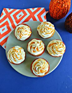 Top view of a plate with 6 cupcakes drizzled with caramel on top of an orange and white napkin with 2 pumpkin behind the plate.