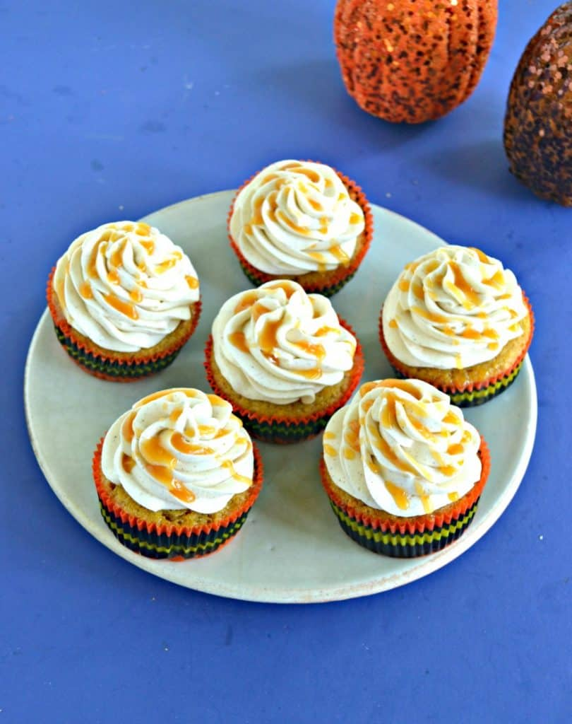 A plate of six butternut squash cupcakes topped with frosting and drizzled with caramel on a blue background with the bottom of a pumpkin showing in the corner.