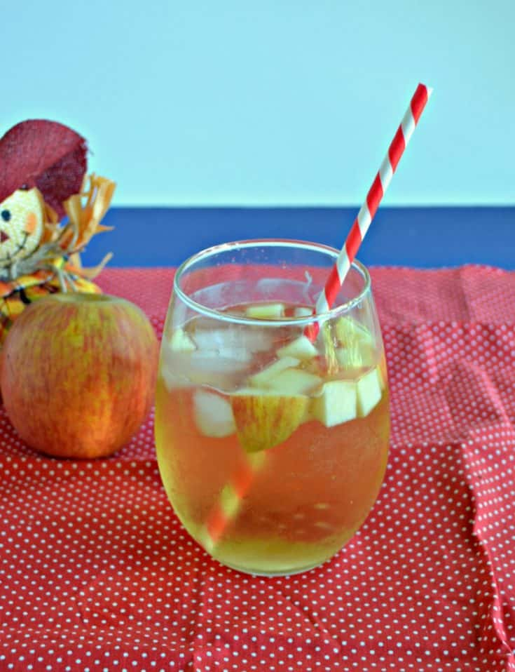 A stemless glass of Caramel Apple Sangria with apple pieces floating in it with a straw sticking out of it on a red background with a scarecrow holding and apple behind the beverage.
