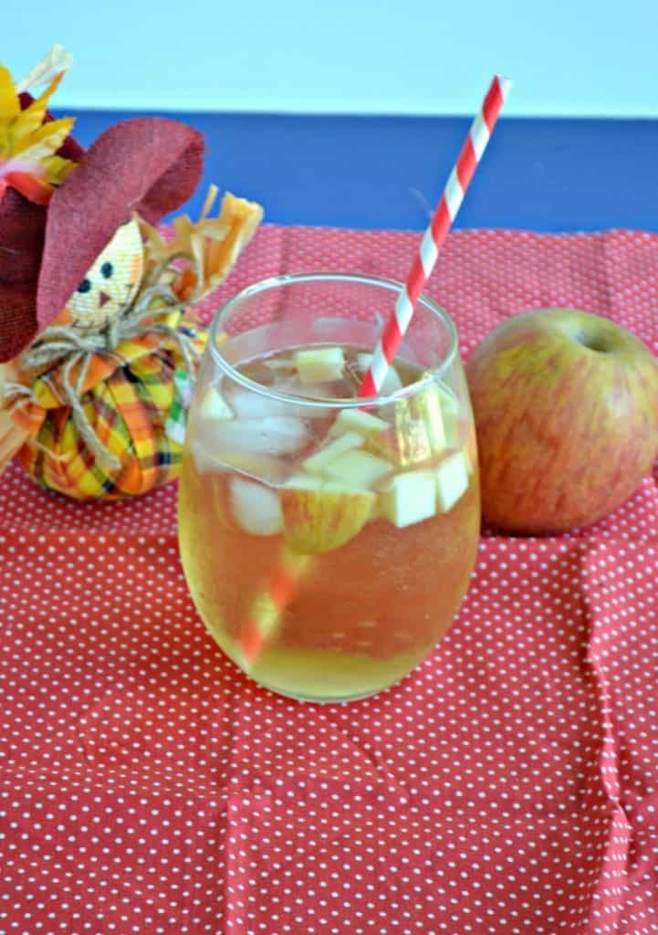 Close up view of a stemless glass of Caramel Apple Sangria with apple pieces floating in it with a straw sticking out of it on a red background with a scarecrow holding and apple behind the beverage.