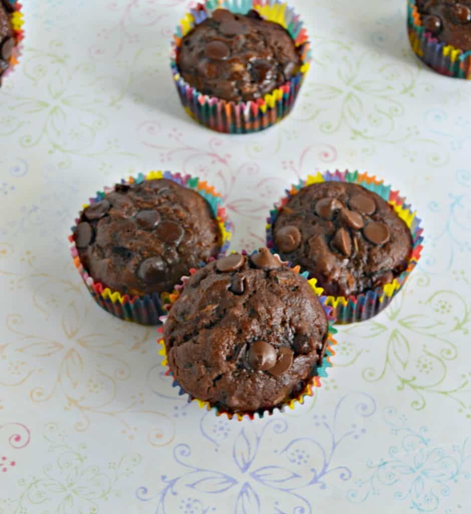 Three chocolate muffins with one in the background all on a white background.