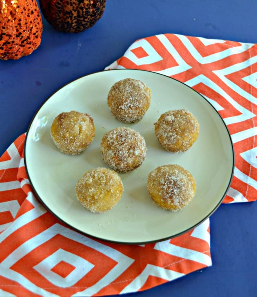 A plate with six donut holes on it in a circle with one in the middle sitting on an orange and white napkin.