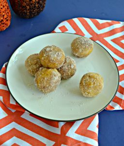 A plate with three donut holes piled with one more on top along with two donut holes on the opposite side of the plate sitting on an orange and white napkin with 2 pumpkins barely showing in the top left hand corner.