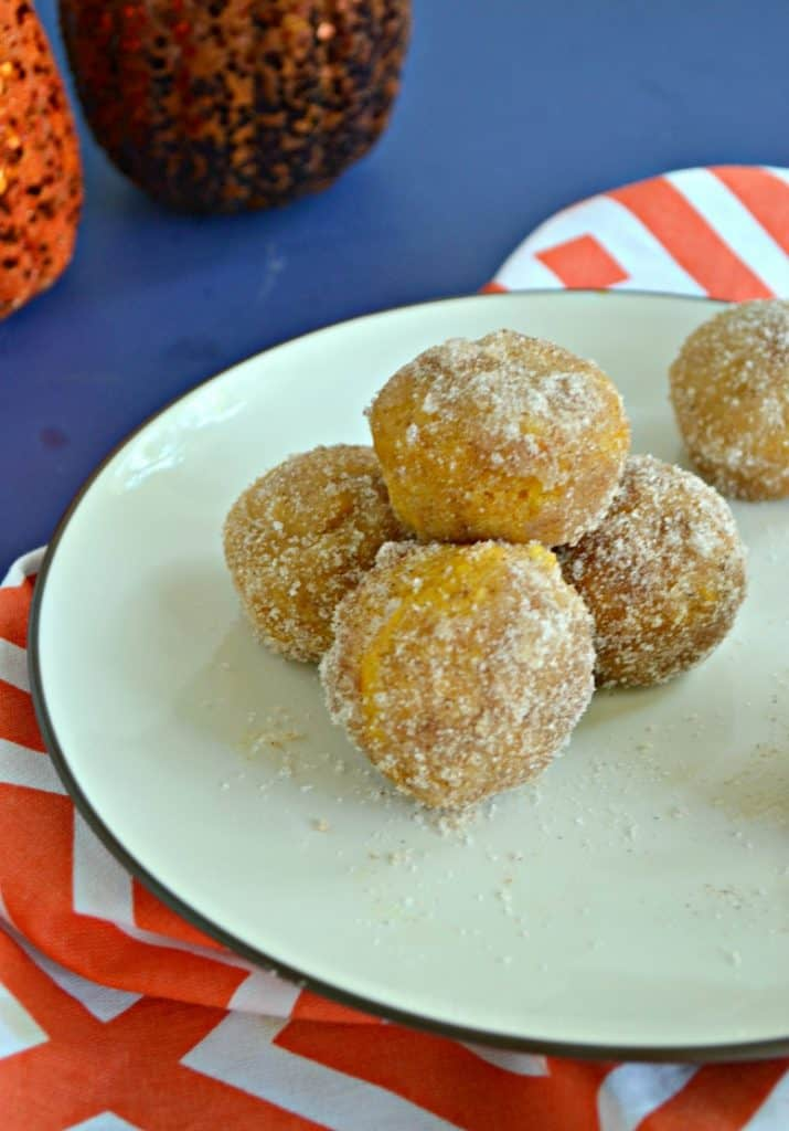 A close up of three donut holes with one donut hole balancing on top sitting on an orange and white napkin.