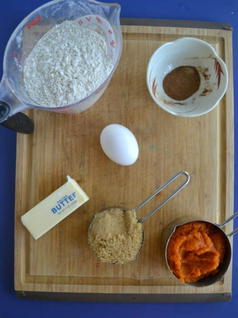 A cutting board with a cup of flour, a small bowl with a spice mixture, one egg, half a stick of butter, a half cup of brown sugar, and a half cup of pumpkin sitting on top of it.