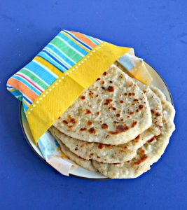 A plate with three Naan flatbread wrapped in an orange, blue, and yellow napkin on a blue background.