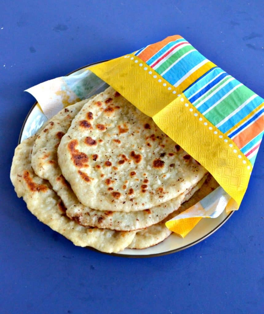 A plate with a stack of Naan wrapped in an orange, yellow, blue, and green napkin on a blue background.