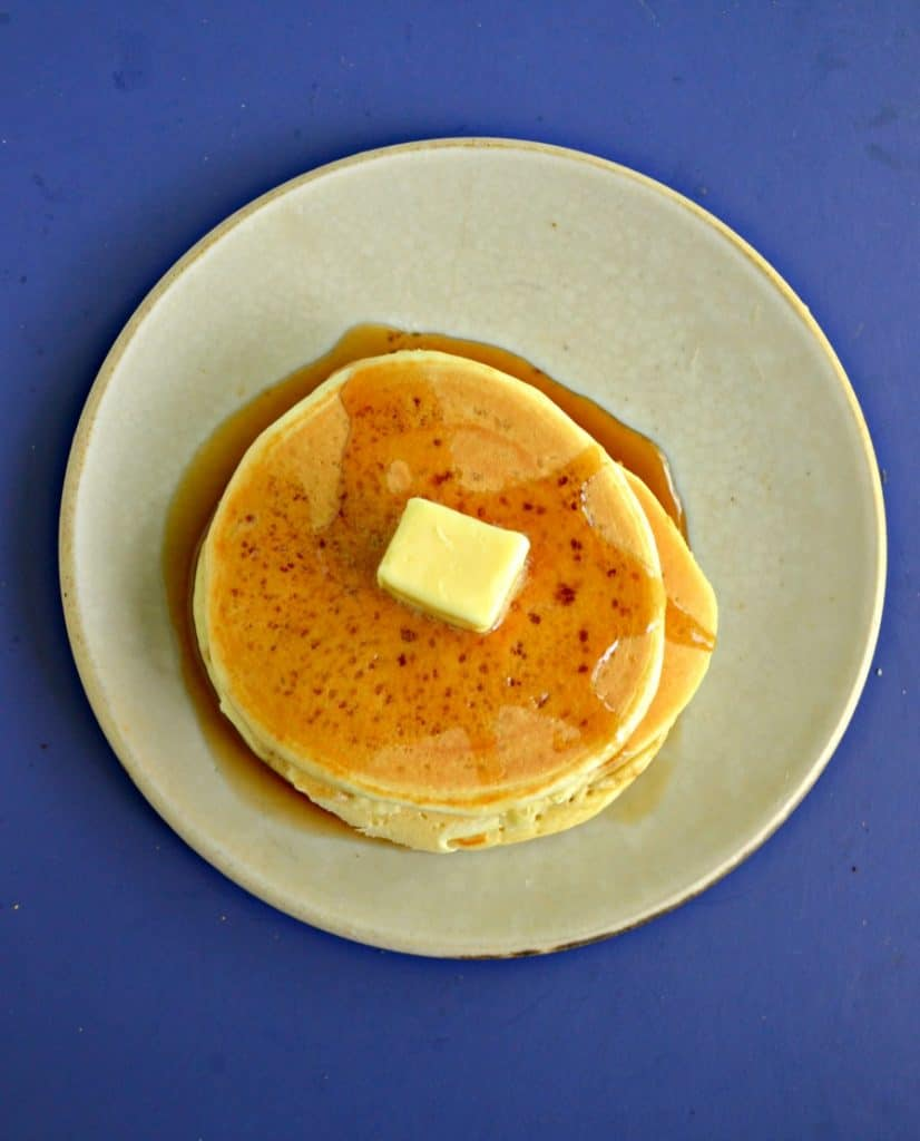 A plate piled with a stack of 3 pancakes on a blue background.