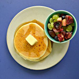 A plate piled high with 3 pancakes topped with syrup and a pat of butter, a bowl of fresh fruit on the side, all on a blue background.