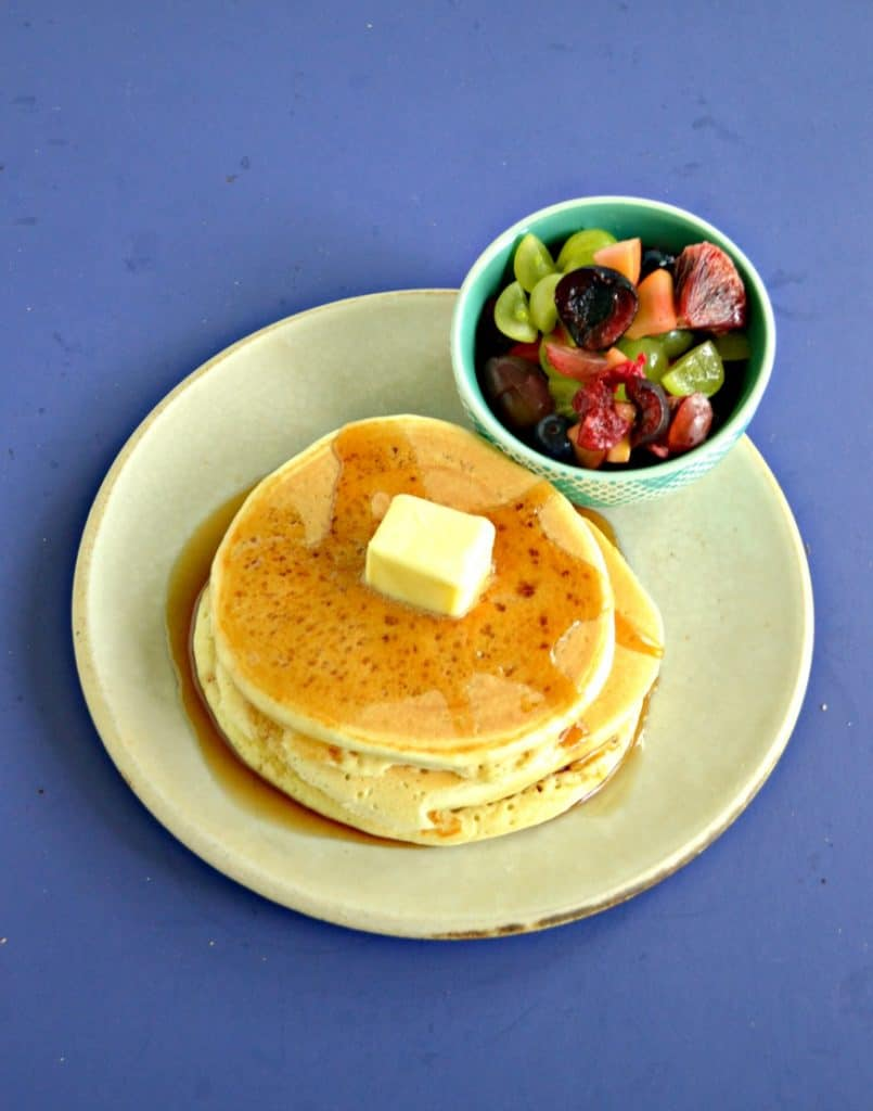 A front view of a plate piled high with 3 pancakes topped with syrup and a pat of butter, a bowl of fresh fruit on the side, all on a blue background.