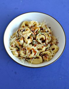 A bowl of tortellini topped with parmesan cheese and a balsamic drizzle on a blue background.