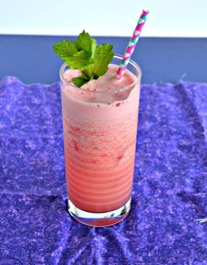 A bright pink cocktail that is frothy on the top with a pink and blue straw coming out of it and a bright green sprig on mint on top on a purple napkin.