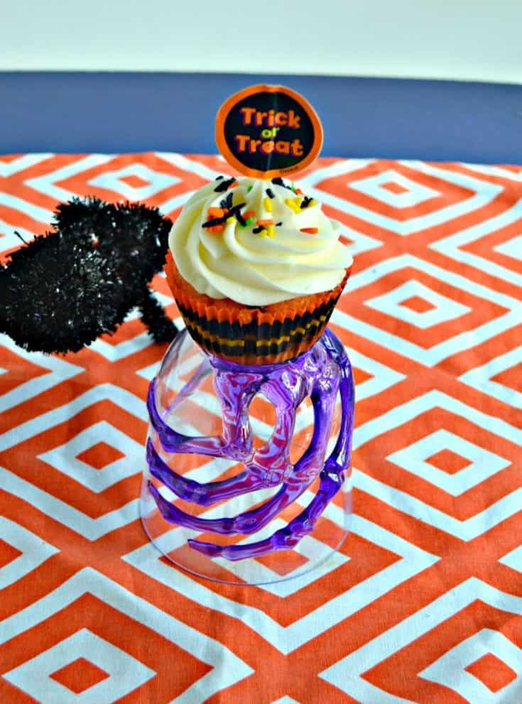 A glass with a purple skeleton hand holding a cupcake with white frosting and a trick or treat topper on top of an orange and white background with a black spider climbing up to the cupcake.