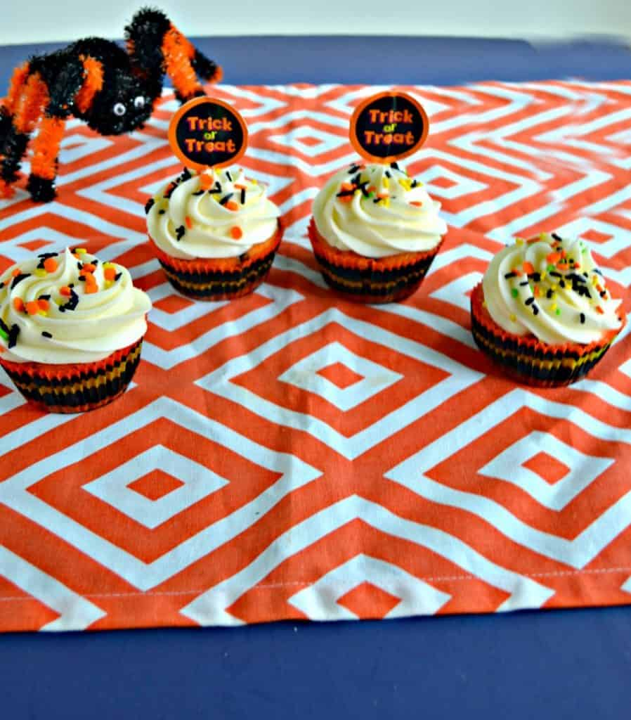 Four cupcakes with white frosting and black and orange sprinkles with a pumpkin topper on an orange and white background with an orange and black spider creeping up on them from the back left.