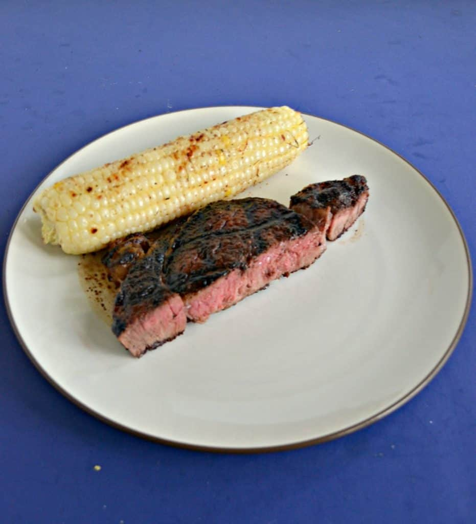 A plate with an ear of corn on the cob with a large piece of steak in front of it that hass grill marks on the top and a pink center with a blue background.