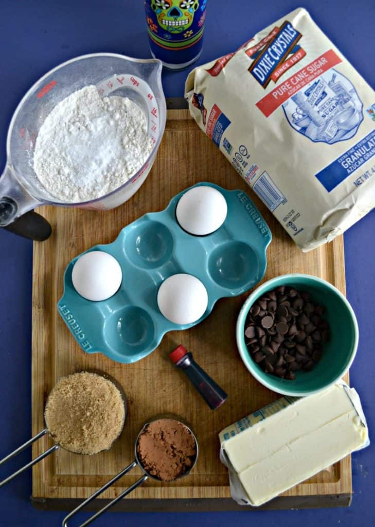 A cutting board topped with a measuring cup of flour, Dixie Crystals sugar in a bag, a blue container with 3 eggs in it, a bowl of chocolate chips, 2 sticks of butter, a measuring cup of brown sugar, and a cup of cocoa powder.