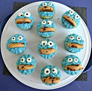 A large white platter scattered with cupcakes decorated like Cookie Monster with blue frosting, google candy eyes, and half a cookie mouth.