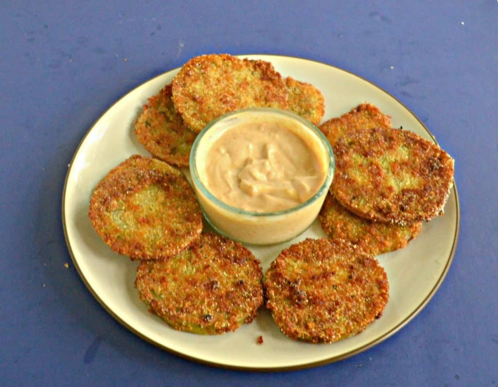 A side view of a plate piled with golden brown fried green tomatoes with a bowl of spicy remoulade in the middle on a blue background.