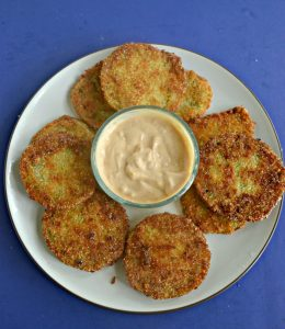 A plate piled with golden brown fried green tomatoes with a bowl of spicy remoulade in the middle on a blue background.