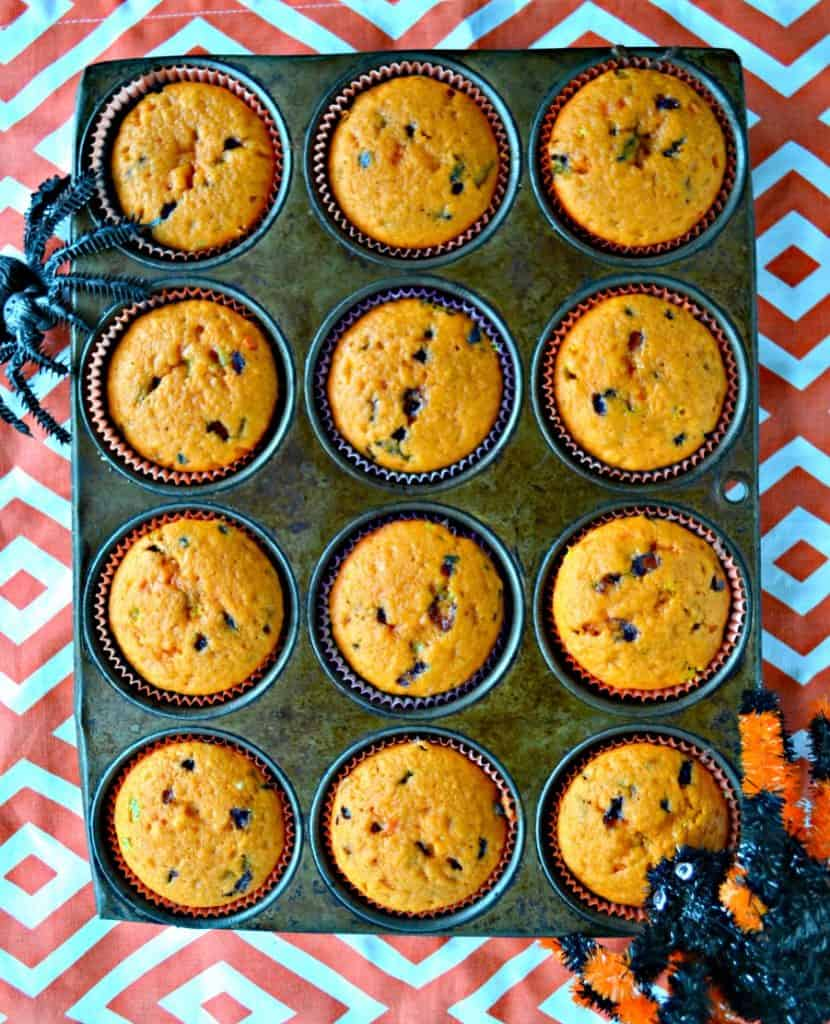 A muffin tin filled with orange cupcakes on an orange and white background with a spider coming onto the muffin tin from the bottom right and top left.