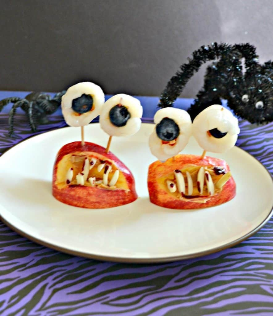 A plate with two monster mouths on it made of apple wedges, eyeballs made out of lychee with blueberries in them, and almond teeth, a spider creeping in from the back right, on a purple and black background.