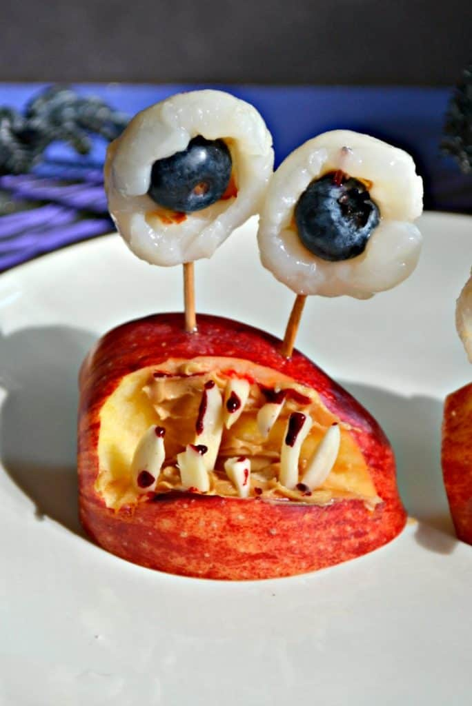 Close up image of a monster mouth made out of an apple wedge with almond sliver teeth, toothpicks coming out of the top spearing lychee and blueberry eyeballs.