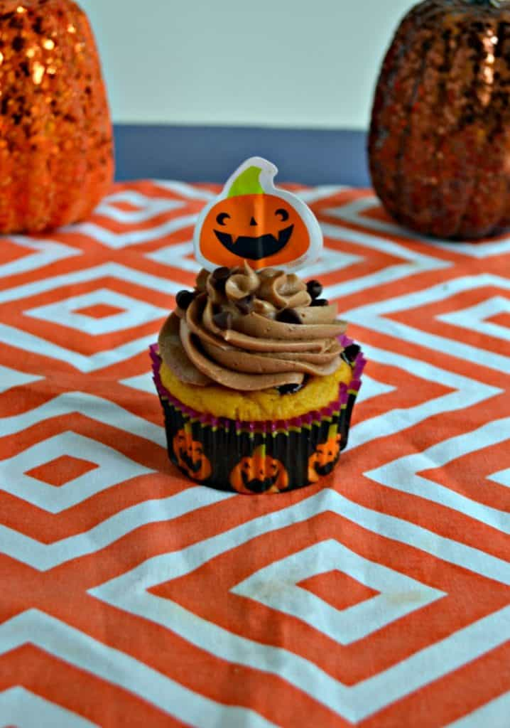 A close up view of a cupcake in a pumpkin cupcake liner topped with chocolate frosting, sprinkled with chocolate chips, topped with a paper pumpkin on an orange and white platemath. There are two pumpkin behind it, one on either side.