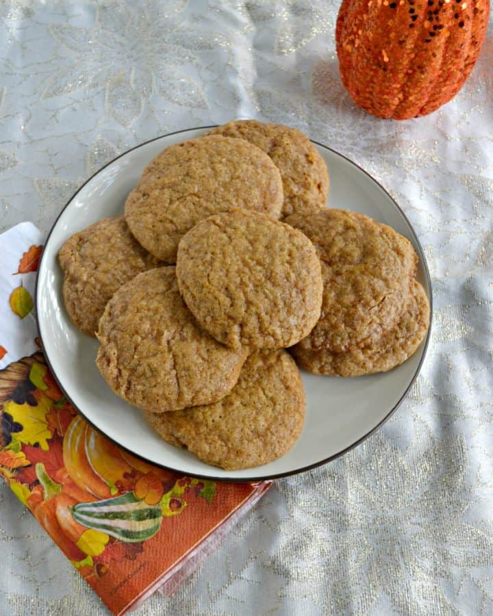 A white plate piled high with snickerdoodle cookies on top of an orange napkin with leaves on it and part of a pumpkin peeking in from the upper right hand corner.