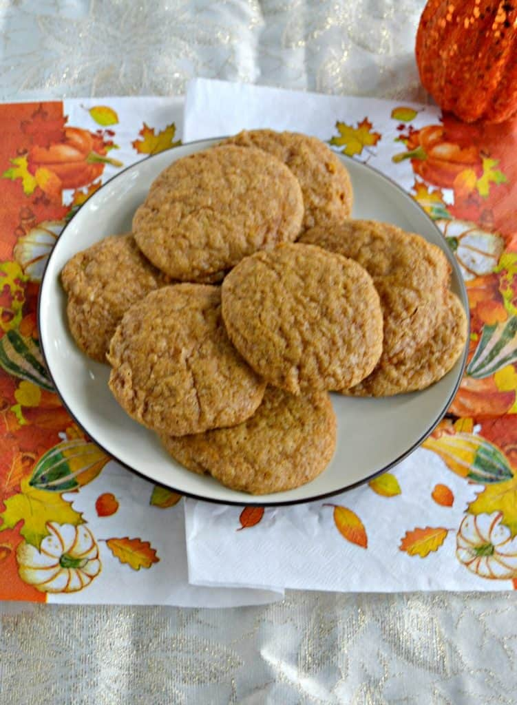 A long white, orange, and yellow napkin with leaves on it topped by a white plate piled high with pumpkin cookies.