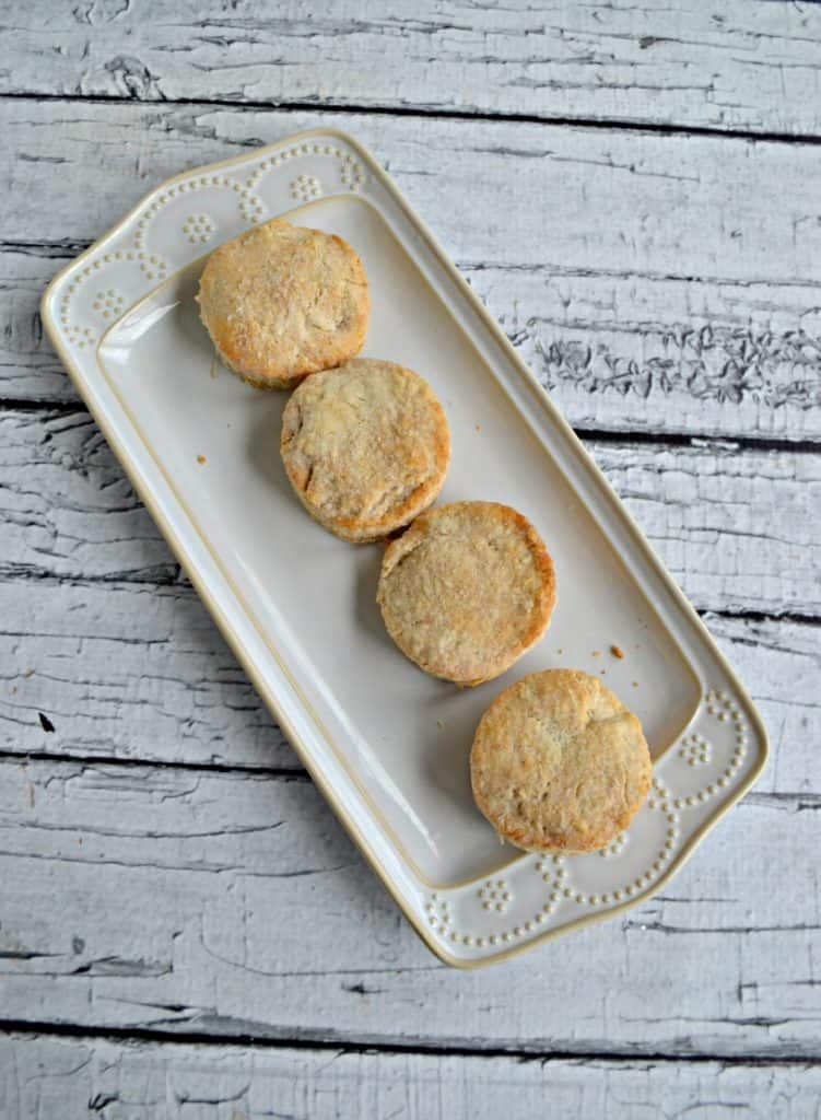 A white plate with 4 biscuits lined up on it on a white wooden backdrop.