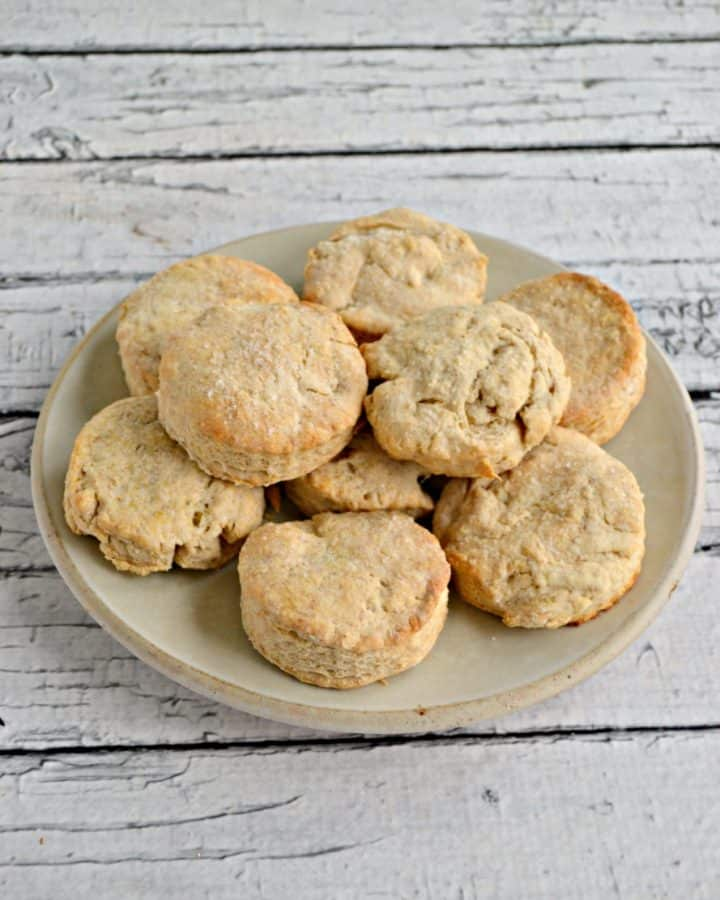 A plate piled high with biscuits on a white wooden background.